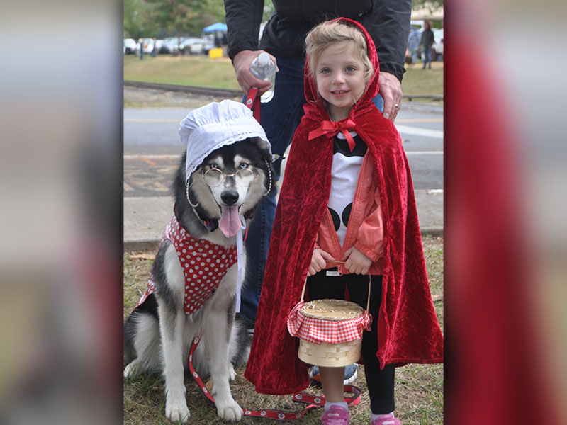 Little Red Riding Hood, Claire, and Big Bad Wolf, Mila, took a break and were all smiles during the annual Paws in the Park in downtown Blue Ridge, Saturday, October 19. Heavy rains didn't dampen spirits for the annual event that included a parade and dock diving dogs.