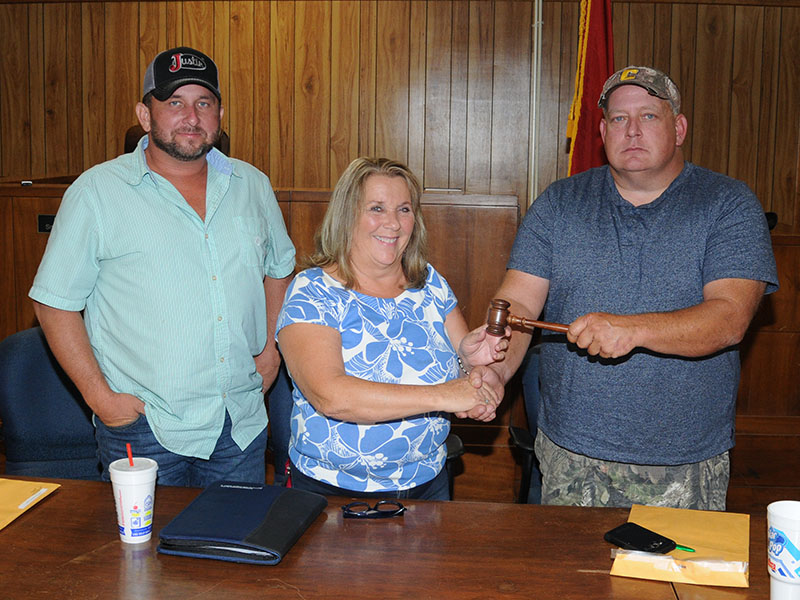 Debbie Davis, who represents District 1, was elected chairwoman of the Polk County Board of Commissioners Thursday, September 26. Here, she receives the gavel from outgoing Chairman Greg Brooks, right. Incoming Vice Chairman Jeremy Kimsey, who represents District 3, is at left.