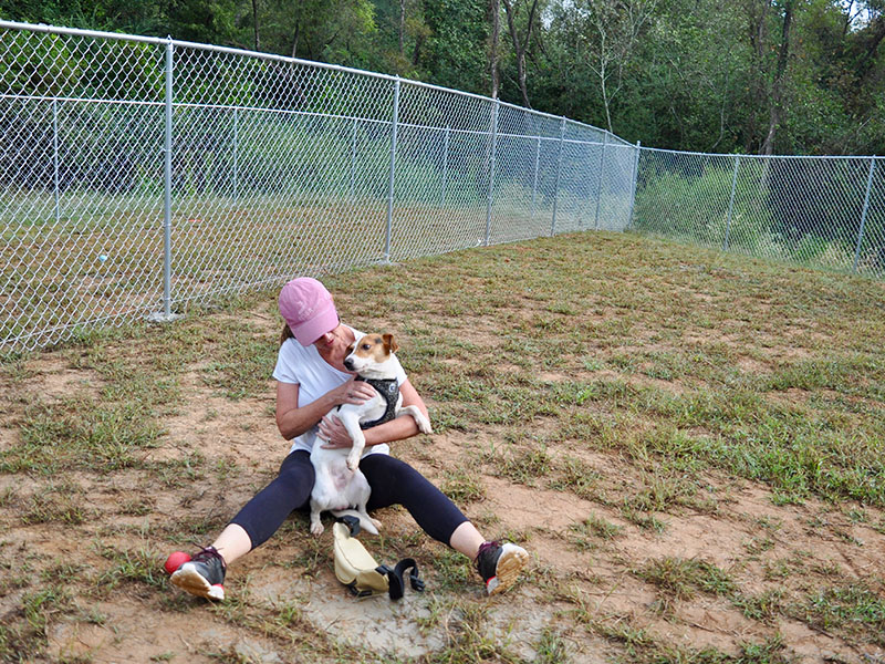 "Fannin County Animal Control volunteer Debbie Williams spends time with one of the facility's residents,""Rocco,"" in Animal Control's recently completed dog run."