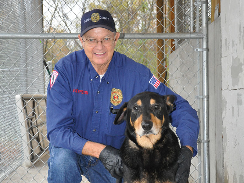 Fannin County Animal Control Officer Pat Patterson kneels beside this big, handsome Shepherd mix who was dropped off by folks who found him on Sunrock Road, October 30. Officers are searching for his owners. If you know where he belongs, call Animal Control as soon as possible. This sweetie has a black coat with striking golden tan markings and floppy ears. He also has a little gray on his muzzle and around his eyes. View this fella under Animal Control number 325-19.