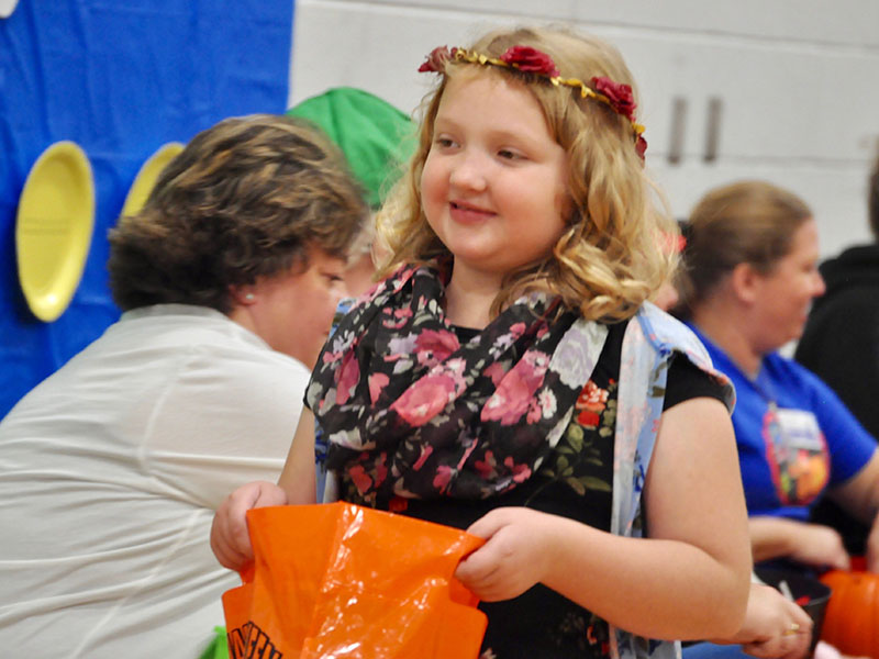 East Fannin Elementary School student River Ayers excitedly walks to get more candy at the school's trick-or-treating event.