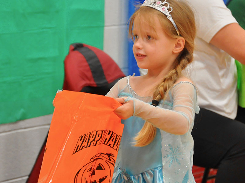 Kelsey Ray holds up her bag as she requests a treat at East Fannin Elementary School's Halloween event.