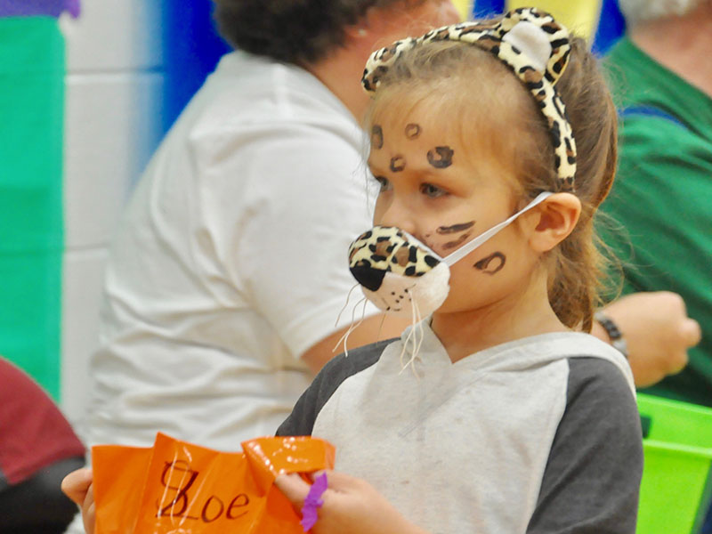 Viktorya-Zoe Lipscomb holds out her trick-or-treating bag to receive candy at East Fannin Elementary School.