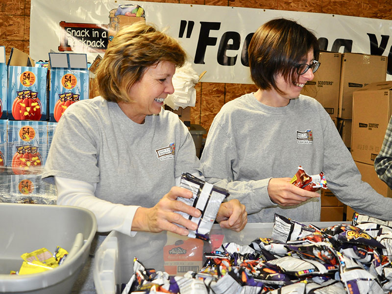 Snack in a Backpack volunteers Mary Langford, left, and Rose Schueneman helped the organization pack their 20,000th meal of the 2019-2020 school year Wednesday, November 20.