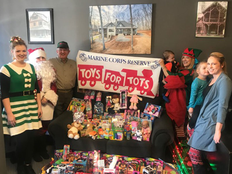 Magalie Dean, from left, Santa, Jim Brumbelow, Ryan Sisson, Tracie Griffith, Claire Sisson and Amber Sisson smile while representing Tru Mountain Reality for this year's First Community Mortgage Toys for Tots Challenge.