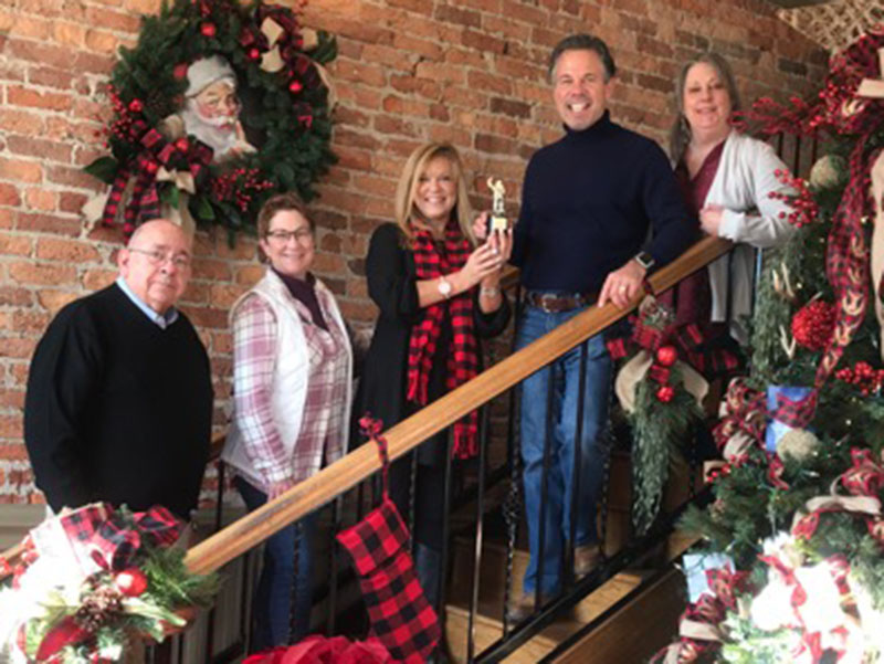 Tracie Griffith, holding trophie, presents a third place trophie to Coldwell Banker. From left, Steven Cockburn, Donna O'Neal, Tracie Griffith, Faron King and Teresa Cronk smile while accepting the award.