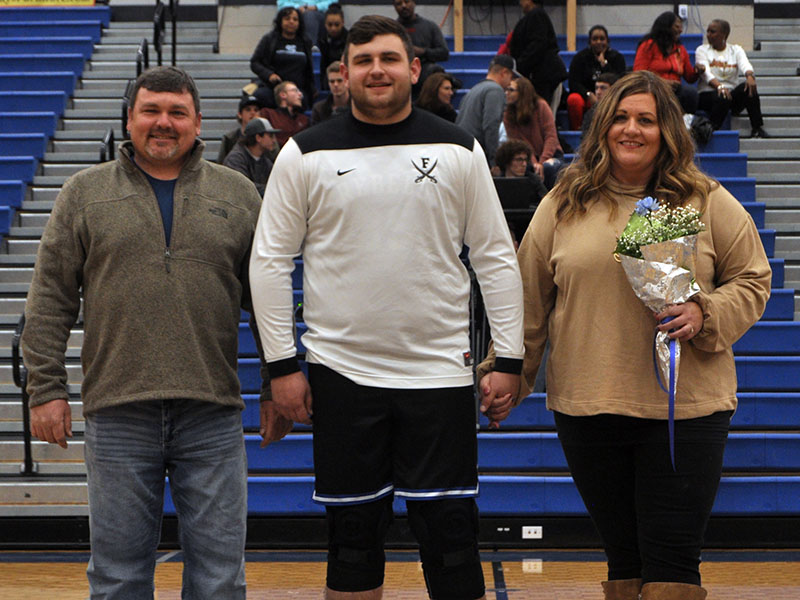 Senior Rebel Miles Johnson was one of eight seniors recognized during Fannin County's last home basketball game of the season Friday, January 31. Johnson is shown with his parents, Earl Johnson and Leslie Mann.