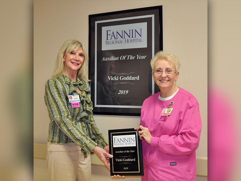Fannin Regional Hospital Auxiliary member Vicki Goddard, right, was named Auxilian of the Year for 2019. She was presented the award by Director of Volunteer Services Susan Kiker in front of a mounted version of the award that hangs in the halls of Fannin Regional Hospital along with other 2019 award recipients.