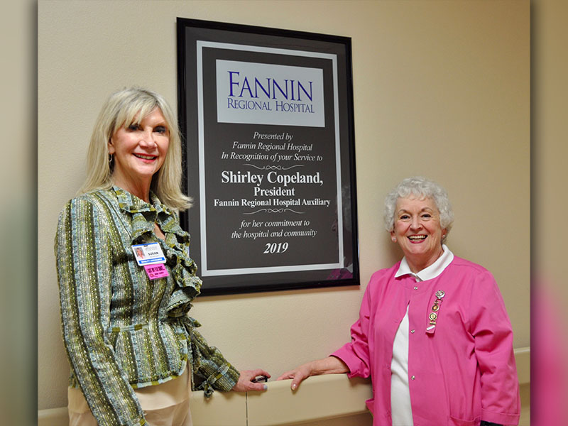 Fannin Regional Hospital Auxiliary president Shirley Copeland, right, stands next to a mounted award recognizing her service to Fannin Regional Hospital and the community during the year of 2019. She is shown with Director of Volunteer Services Susan Kiker.