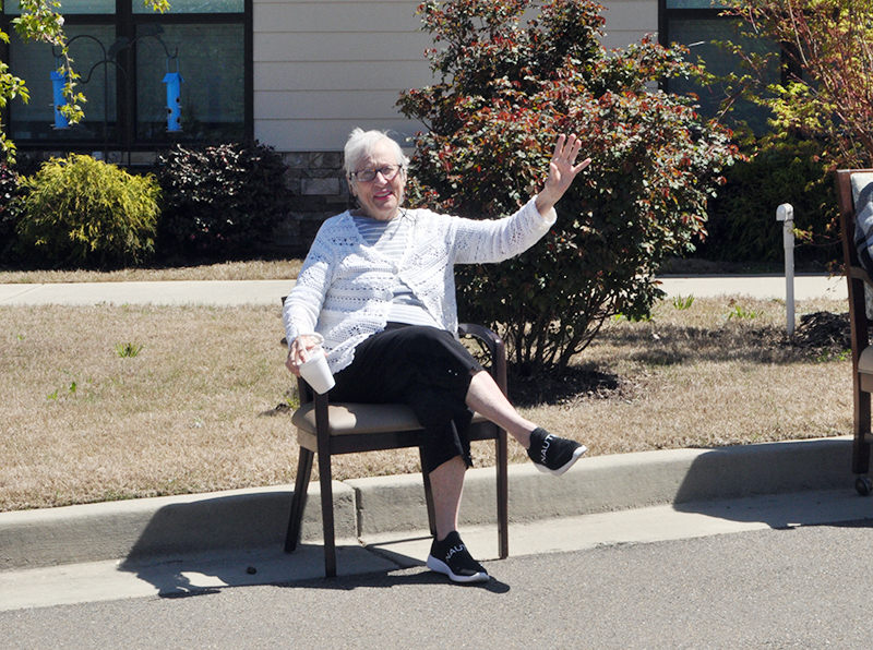 Carolyn Pierce waves as she waits on the parade to start at Blue Ridge Assisted Living & Memory Care Friday, April 3.