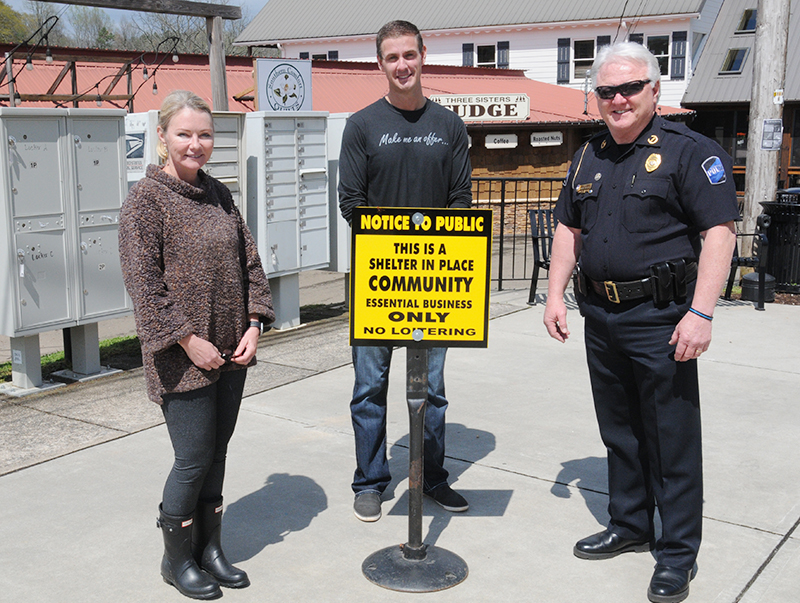 Blue Ridge City Council members Rhonda Haight and Nathan Fitts, and Police Chief Johnny Scearce, from left, are shown with one of the signs placed downtown to remind everyone to shelter in place.