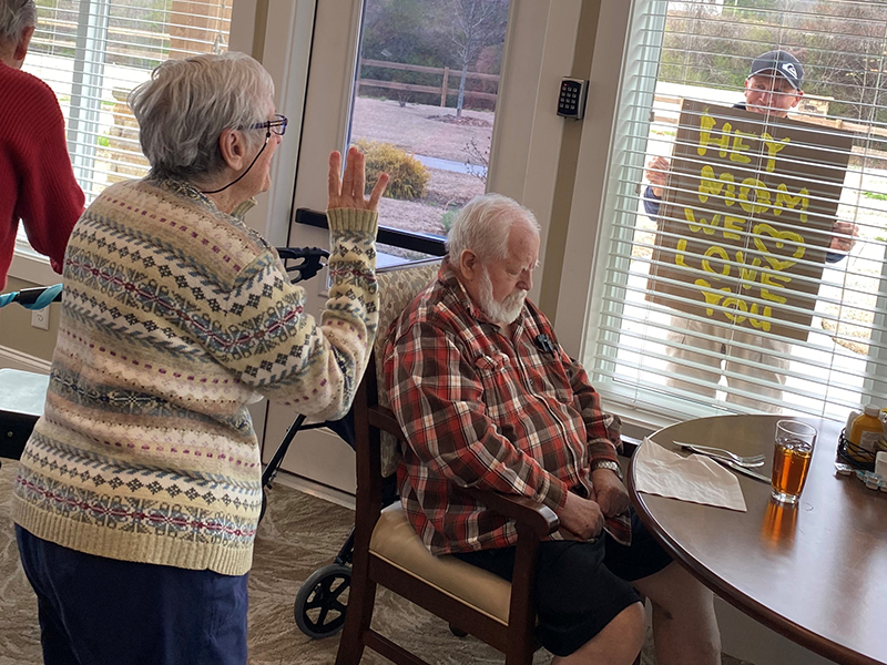 Blue Ridge Assisted Living & Memory Care resident Carolyn Pierce waved to her sons, Jeff and Ryan Pierce, who made signs to cheer her up from afar.