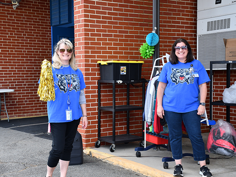 East Fannin Elementary School Physical Education Teacher Kathy Culpepper, left, and STEM Teacher Christie Holtman cheer on fifth grade students as they drive through the school's Fifth Grade Parade Thursday, May 22.