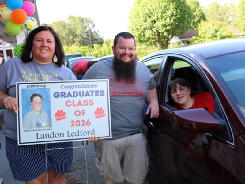 CBES teachers Jennifer Speights and Andrew Cook give sixth grade graduate Landon Ledford his things during the drive-thru graduation Tuesday, May 26.