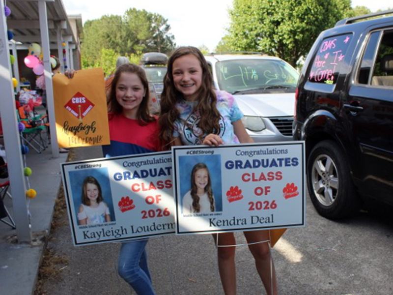 Copper Basin Elementary School graduates Kayleigh Loudermilk and Kendra Deal show off their signs at the CBES drive-thru graduation Tuesday, May 26.