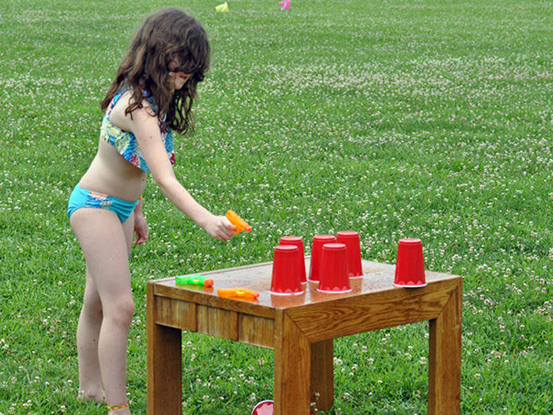 Violet Miller tries her luck at shooting red solo cups over with a water gun during the Fannin Recreation Center's summer camp, Wednesday, July 8.