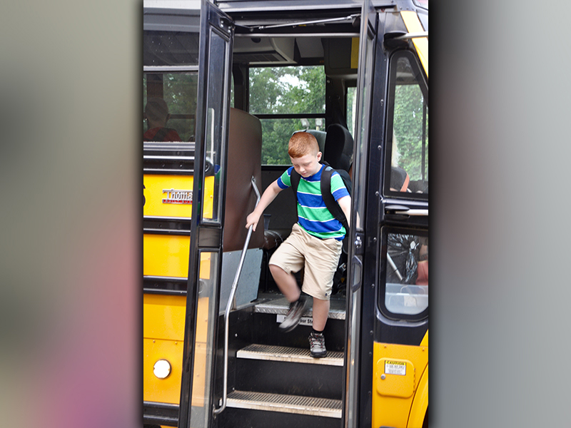 Zeke Payne shuffles to get off of the school bus at Blue Ridge Elementary School on the first day Friday, August 7.