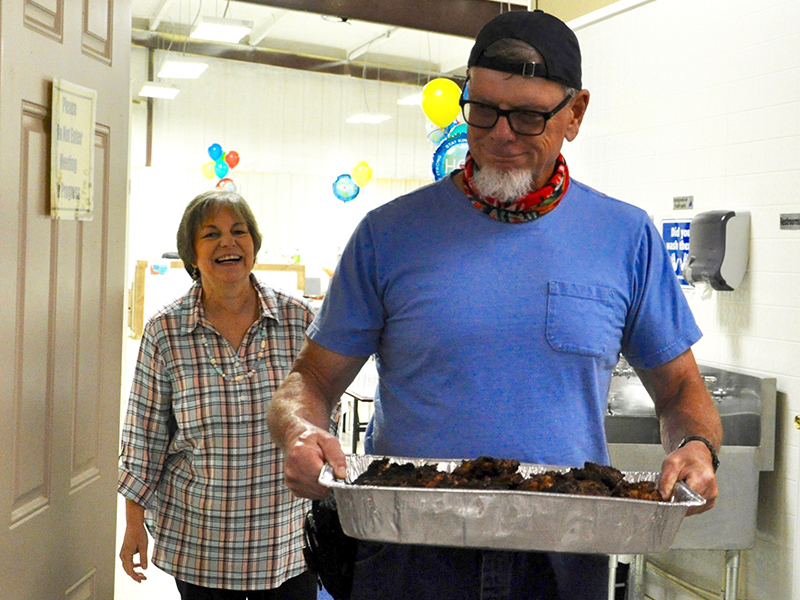 A volunteer appreciation lunch was hosted by Fannin County Family Connection to show appreciation for their volunteers, on the anniversary of the move-in day at their current facility. Jim Yacavone carries in a pan of grilled chicken while Executive Director Sherry Morris smiles wide.