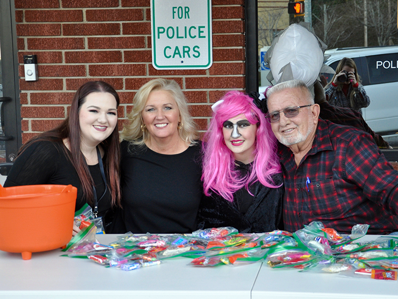 Kaylee Robertson, from left, Judy Earley, Madison Earley and City of McCaysville Mayor Thomas Seabolt smile while passing out candy in front of the McCaysville Police Department Saturday, October 31.