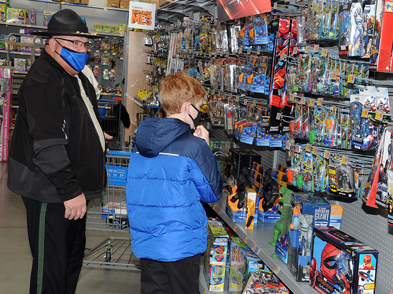 Fannin County School Resource Officer Deputy Tracy Summers helps a youngster select his gifts during Shop With A Cop Saturday at the Blue Ridge Walmart.