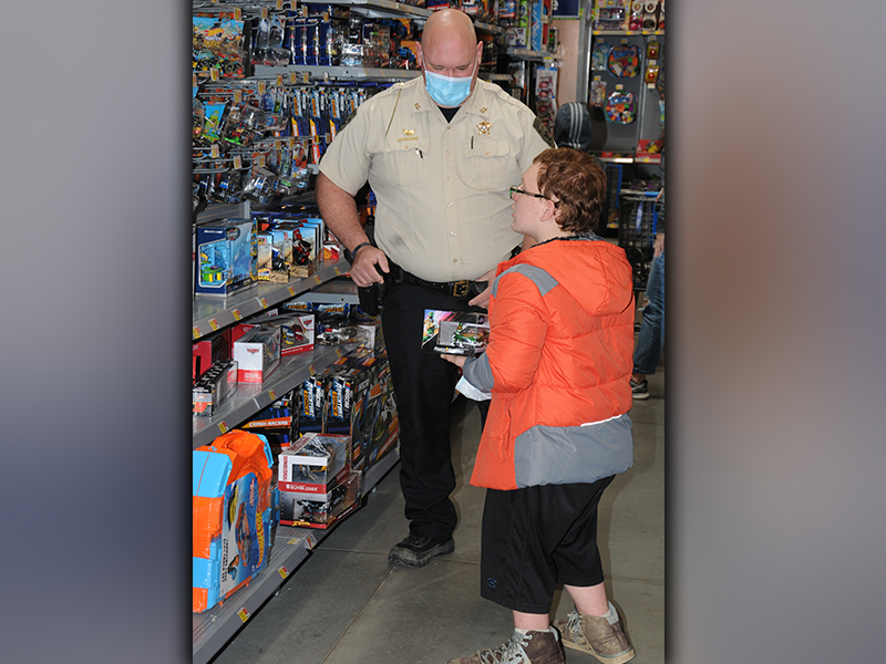 Fannin County Deputy Sheriff Corporal John Kinser helps a youngster pick out the perfect Christmas gift during Shop With a Cop. A total of 87 children were served by the program this year.
