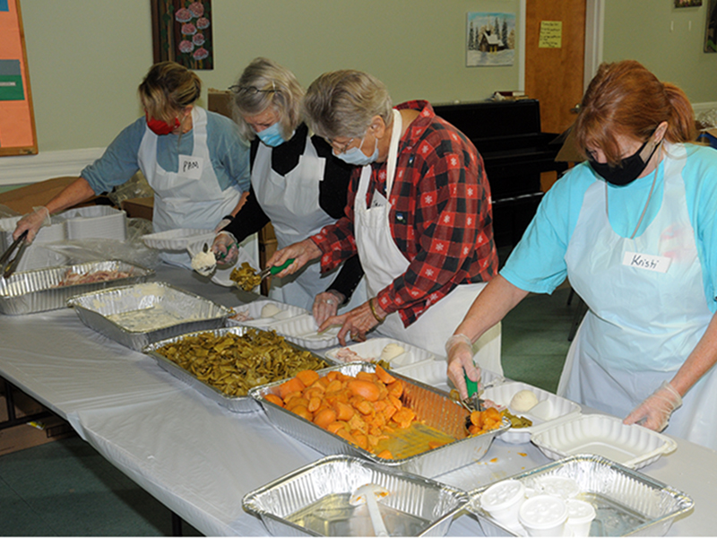 Pam Smith, Carolyn Howard, Sandy Daugherty and Kristi  Buchanan, from left, volunteered for the Good Samaritans's annual Open Table event, which was held Thanksgiving Day at the Fannin County Senior Center. This year the event had to be changed from the annual sit-down, festive occasion to a drive-thru offering. These volunteers were busy preparing plates for hungry participants.