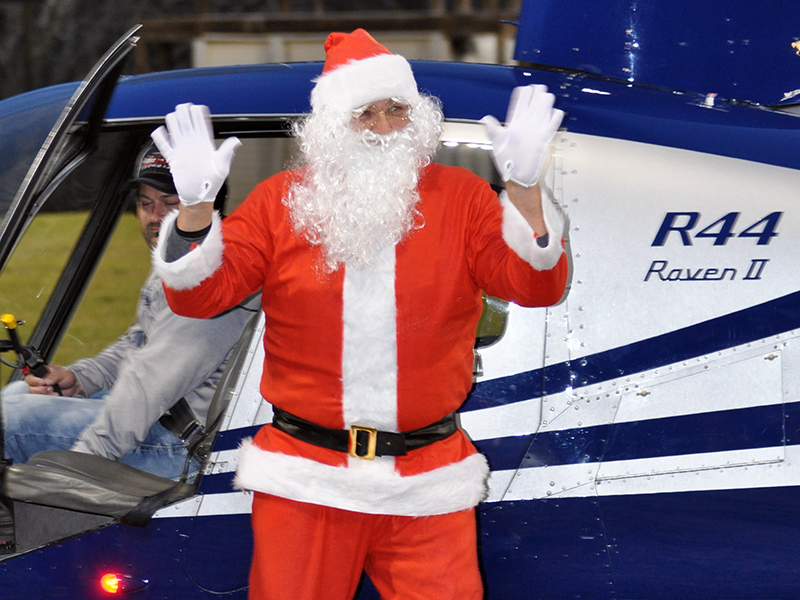 Santa Claus waves to everyone as he steps out of the helicopter that carried him to his visit at the Fannin County Recreation Center.