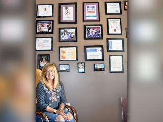 Tracie Griffith, owner and mortgage broker of First Community Mortgage, sits next to the office's wall showcasing many of the causes the business has sponsored and supported over the years, such as Relay for Life, St. Jude and Toys for Tots.