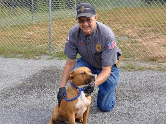 Animal Control officer Pat Patterson smiles while showing off this male Boxer mix who was dropped off September 17. He will remain at Animal Control until reclaimed or adopted. This handsome boy has a light brown coat with a white chest and paws. View him under Animal Control number 275-19.