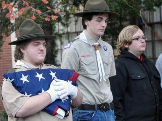 Jonothon Payne, Ducktown Boy Scout Troop 14's assistant scout master, holds the first flag to be retired the evening of Saturday, November 9. Shown with Payne are, from left, Matthew Payne and Dakota Harris.