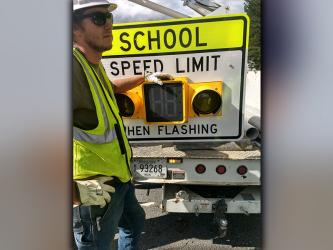 A worker from Nabco Electric is shown with one of the flashing school zone lights installed on Highway 68 in front of the entrance to Copper Basin schools.