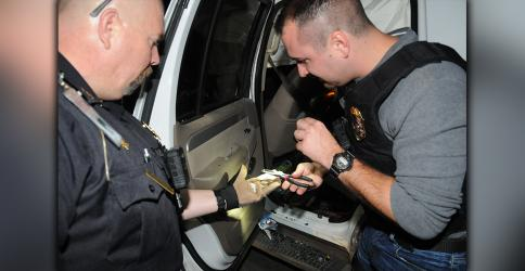 McCaysville Police Chief Mike Earley, right, used needle-nosed pliers to pick shards of crystal methamphetamine from a suspect's wrecked vehicle Saturday night in McCaysville. Detective Cory Collogan, along with other McCaysville officers, helped collect the evidence, which includes 16  and 1/2 grams of heroin.
