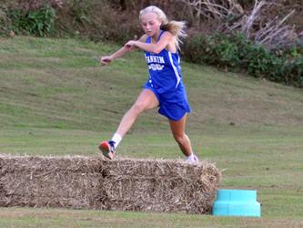 Carlee Holloway hurdles an obstacle during the Lady Rebels cross country meet Wednesday, October 21.